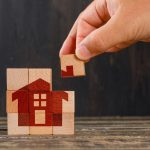 Stay at home concept on wooden background side view. hand holding wooden cube.
